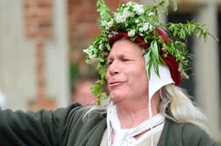 Mature man in May Day head dress presenting medieval Mayday play Royalty Free Stock Photography