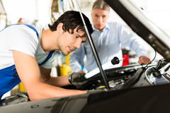 Mature man and mechanic looking at car engine. Mature client and young mechanic looking under car hood at engine with lamp stock images
