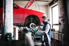 Man mechanic repairing a car in a garage. Mature man mechanic repairing a car in a garage Stock Images