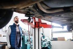 Man mechanic repairing a car in a garage. Mature man mechanic repairing a car in a garage Royalty Free Stock Images