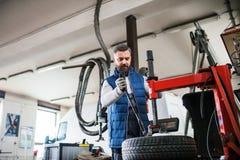 Man mechanic repairing a car in a garage. Mature man mechanic repairing a car in a garage Stock Image