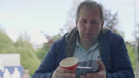 Mature man messages someone on his smartphone sitting at table stock video footage