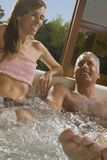 A mature man with a mid adult woman in a jacuzzi stock images