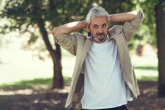 Mature man, model of fashion, in an urban park. Royalty Free Stock Photography