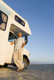 Mature man by motor home on beach, arm on door, low angle view Stock Photos