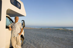 Mature man by motor home on beach, arm on window, portrait, low angle view Stock Photography