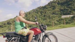 Mature man motorcyclist traveling on motorbike on tropical nature landscape. Senior man driving on motorcycle in. Mature man motorcyclist traveling on motorbike stock video