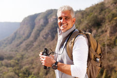Mature man mountain. Smiling mature man on top of the mountain stock photography