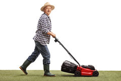 Mature man mowing a lawn. Profile shot of a mature man mowing a lawn with a lawnmower isolated on white background stock photography