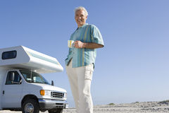 Mature man with mug by motor home on beach, smiling, portrait, low angle view Stock Photo