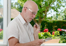 Mature man near a window taking notes Stock Images