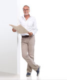 Mature man with newspaper leaning against a wall Royalty Free Stock Image