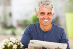Mature man newspaper. Portrait of mature man reading newspaper at home Stock Images