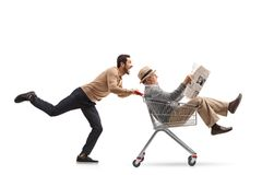 Mature man with a newspaper riding inside a shopping cart being Stock Photo