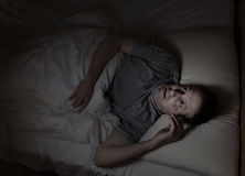 Mature man not able to fall asleep during night time. Top view image of mature man restless in bed from insomnia Stock Images