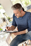 Mature man noting appointment on agenda Royalty Free Stock Photos