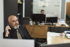 Mature man in office working at phone stock photography