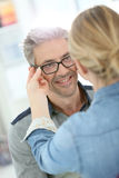 Mature man in optical store trying eyeglasses Stock Photo