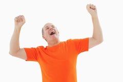 Mature man in orange tshirt cheering Stock Images