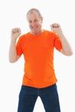 Mature man in orange tshirt cheering Royalty Free Stock Image