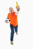 Mature man in orange tshirt holding football and beer. On white background royalty free stock photography