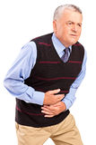 Mature man overwhelmed with a pain in the stomach. Isolated on white background Stock Image