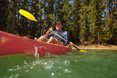 Mature man paddling a kayak in a lake Royalty Free Stock Photo