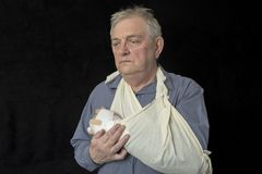 Mature man in pain and holding an injured arm. Taken on a black background royalty free stock photo