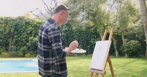 Man painting on canvas in the garden 4k. Mature man painting on canvas in the garden 4k stock video