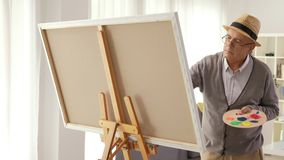 Mature man painting on a canvas stock video footage