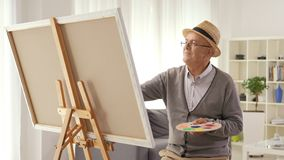 Mature man painting on a canvas with a paintbrush stock footage