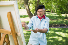 Mature man painting in park Royalty Free Stock Photography