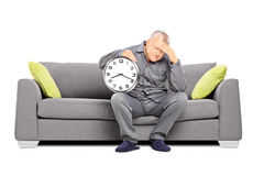 Mature man in pajamas holding a clock and having a headache. Mature man in pajamas seated on a sofa holding a clock and having a headache isolated on white Stock Photography
