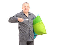 Mature man in pajamas holding a tooth brush and a pillow Stock Photos
