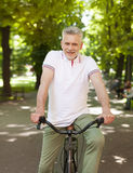 Mature man in the park. Portrait of mature man on the bike royalty free stock images