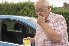 Mature man with parking fine looking annoyed. And fed up stock image