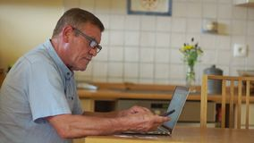 A mature man pays bills using a laptop. Modern technologies and people of retirement age.  stock video