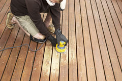 Mature man performing maintenance on home wooden deck. Horizontal photo of mature man kneeling while sanding outdoor wooden deck Stock Photo