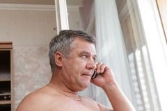 Mature man with phone Royalty Free Stock Photos