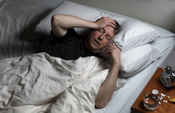 Mature man in physical pain while trying to fall asleep. Mature man with hand on forehead while trying to sleep in bed. Insomnia concept with pain medicine on Royalty Free Stock Photos