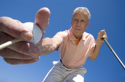 Mature man placing golf tee in grass on golf course, holding golf ball and club, close-up, upward view (wide angle) Stock Images