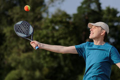 Man playing beach tennis. Mature man playing beach tennis on a beach Royalty Free Stock Photo