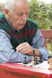 Mature man playing chess Stock Images