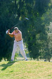 Mature man playing golf, swinging golf club above head (blurred motion) Royalty Free Stock Photo