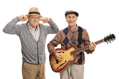 Mature man playing a guitar with another man plugging his ears. Mature men playing a guitar with another men plugging his ears with his fingers isolated on white Stock Photo