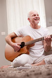 Mature man playing guitar at home Royalty Free Stock Photos