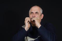 Mature man playing mouth organ Stock Images