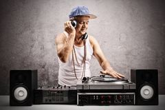 Mature man playing music on a turntable royalty free stock image