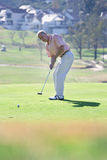 Mature man playing putting shot on green in mid-distance, focus on background Royalty Free Stock Photos