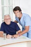 Mature Man playing Sudoku Puzzle Stock Photography